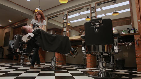 The woman is a professional hairdresser lowers the chair, the camera moves with Footage