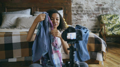 Cheerful african american girl teenager recording video blog about her wardrobe Live Action