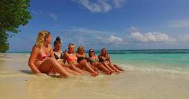 v12695 sunbathing group of young beautiful girls on white sand beach in aqua Live Action