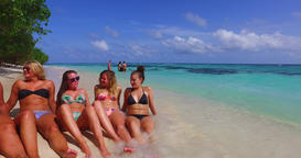 v12700 sunbathing group of young beautiful girls on white sand beach in aqua Live Action