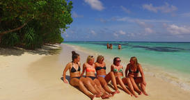 v12703 sunbathing group of young beautiful girls on white sand beach in aqua Live Action