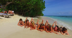 v12742 sunbathing group of young beautiful girls on white sand beach in aqua Live Action