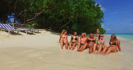 v12746 sunbathing group of young beautiful girls on white sand beach in aqua Live Action