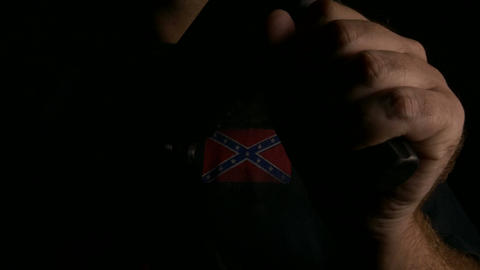 Anonymous man with assault rifle wearing confederate flag t-shirt dolly GIF