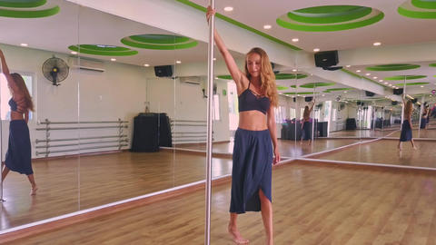 Blonde Girl Rises up Spins on Pole to Music in Hall Center Live Action
