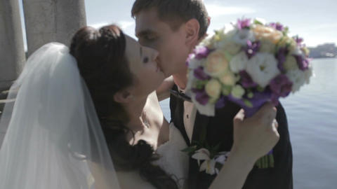 Newlyweds kiss on lake background Footage