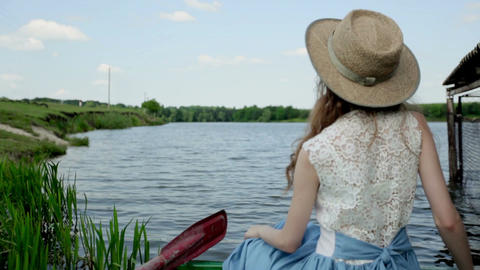girl turns her head. beautiful girl by the lake. girl in a hat near a lake 画像