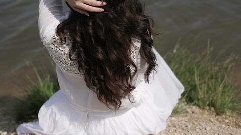 Beautiful brunette woman with long hair sit relax on river bank, play with her Archivo
