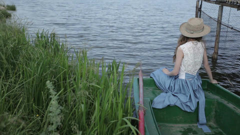 girl turns her head. beautiful girl by the lake. girl in a hat near a lake Footage