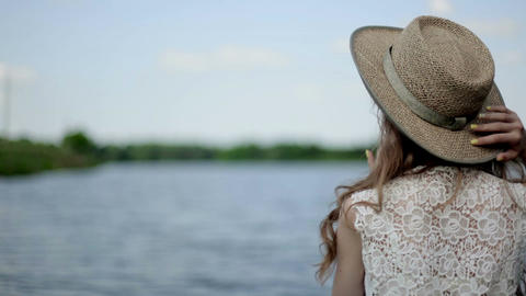 girl turns her head. beautiful girl by the lake. girl in a hat near a lake Image