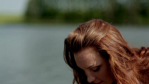 Red-haired girl straightens her hair/ red-haired girl on the bank of the river GIF