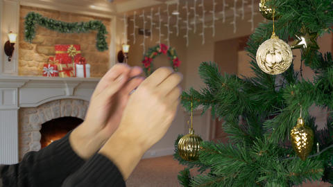 Mans hand decorate christmas tree. Living room background. Yellow sphere ball Footage
