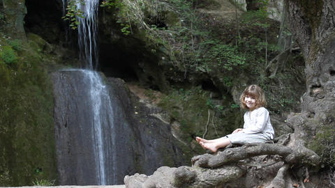 little girl sitting next to a waterfall Footage