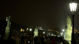night charles bridge with walking people - night city in background - lamp (ligh Footage