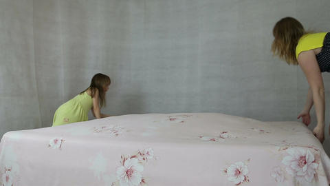 Mother with daughter make the bed bed sheets Footage