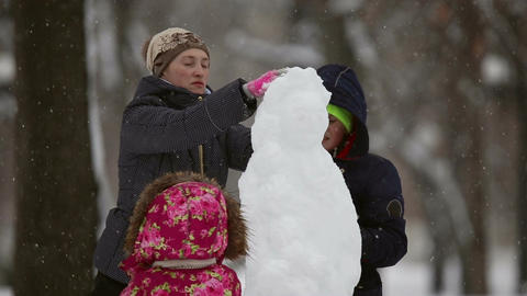 Happy family sculpts snowman out of snow Footage