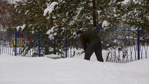 Man cleans snow shoveling Live Action