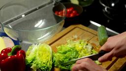 man prepares salad - man sliced lettuce Footage
