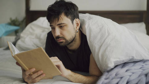 Handsome young man reading a book lying in bed under blanket at home Footage