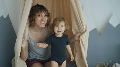 Happy mother with young cute daughter playing and and hide behind curtain at Footage