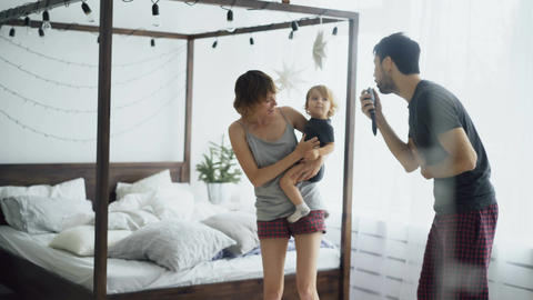Happy family and little cute daughter dancing near bed in bedroom while famter Footage