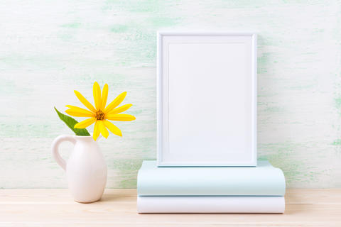 White frame mockup with bright yellow flowers and books Foto