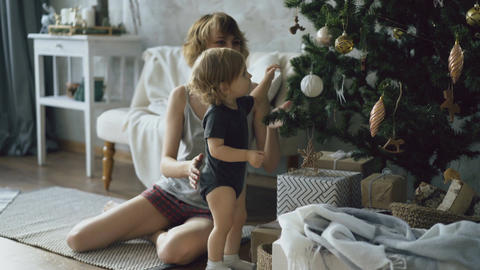 Happy mother and her little daughter playing near the Christmas tree at home Footage