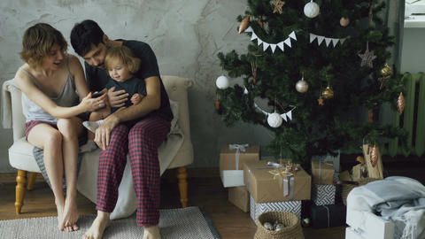 Happy family with cute little daughter sitting near Christmas tree and using Footage