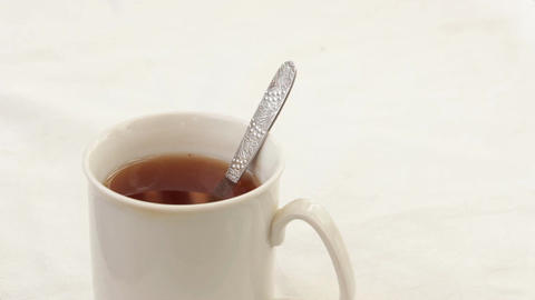 Pour into a cup of tea sugar with a teaspoon Archivo