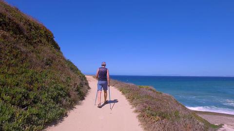 Man Uses Sticks for Scandinavian Walking on the Beautiful Sea Shore Footage
