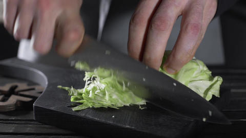 Chef shreds cabbage for vegetable salad, vegetarian meal, vegan food, cooking Footage