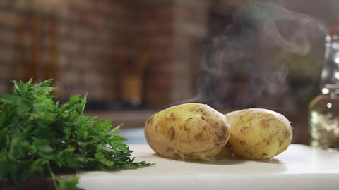 Hot boiled potatoes on the kitchen board, hot steam, boiled vegetables, dish Live Action
