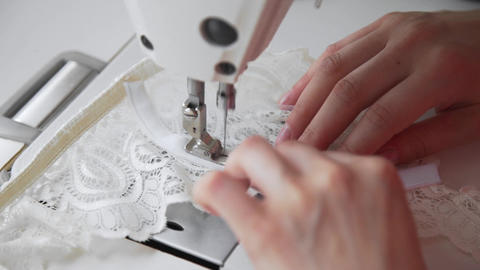Tailor sews lingerie on a sewing machine, thread and lace, handmade underwear Live Action
