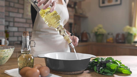 The cook adds sunflower oil to the pan, cooking food, cooking, baking in the Live Action