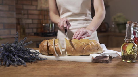 The cook cuts white bread on the kitchen table, bread and bakery, cooking food Footage