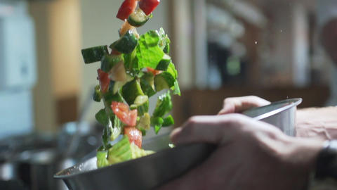 The cook mixes salad with vegetables by throwing it up in slow motion, cooking Footage