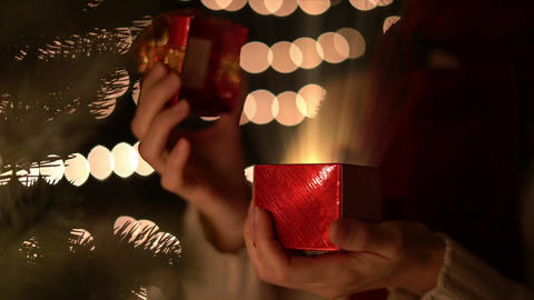 Woman opening red Christmas gift box with golden magical light Live Action