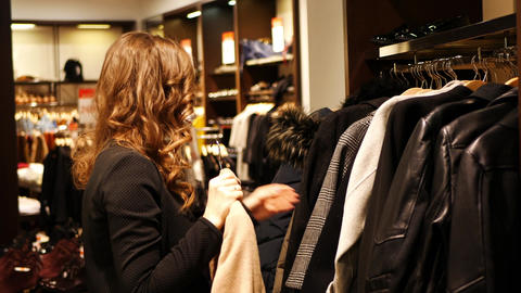 Women choose coat in a clothing store ビデオ