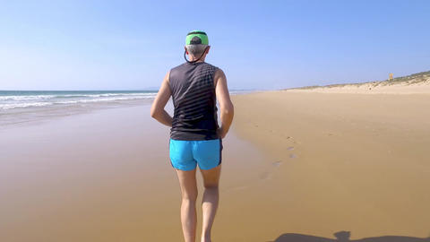 Adult Man in Shorts with a T-shirt Jogging on Ocean Beach Footage