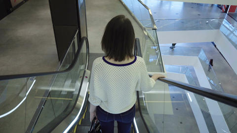 Woman goes down on an escalator Filmmaterial