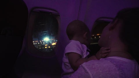 Mother and baby look out of side window. Airpllane takes off over night city Footage