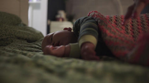 Adult covers sleeping baby with crochet plaid Stock Video Footage