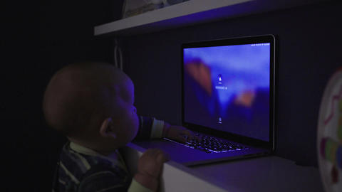 Baby boy pushes the button on laptop keyboard and types a password Footage