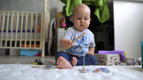 Сute baby boy plays with magnet fishing rod and is happy to catch a toy fish Footage
