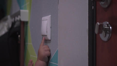 Baby turns off switch on a wall and lights go out. Close up shot of child's hand Footage