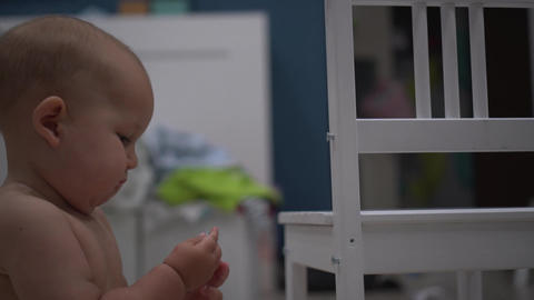 Little baby with a tool tries to tighten a screw in a chair Footage