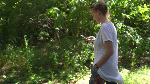 Woman scrolls touch screen of her cell phone while walking in a park. Handheld Footage
