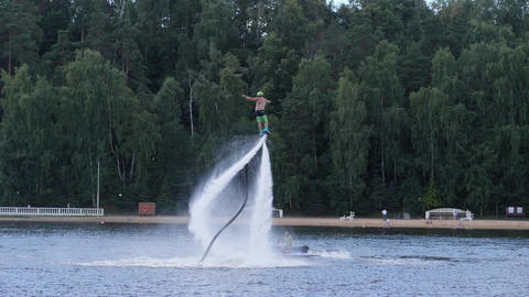 Man on flyboard spins round above the water surface Footage