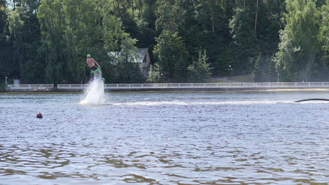 Man on flyboard dives and comes up from the water Footage