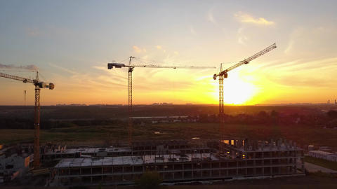 Building cranes at construction site against sunset sky. Aerial shot ビデオ